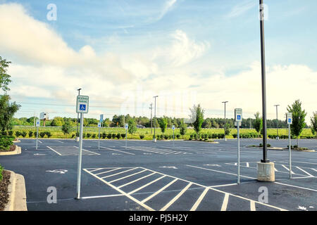 Multiple or numerous empty handicap parking spaces with warning signs in shopping center parking lot or car park in Montgomery Alabama, USA. - Stock Image