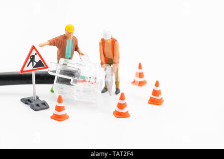 Macro shot on miniature figures as technicians working on the internet web network repair cable socket, isolated on white background. Information tech - Stock Image