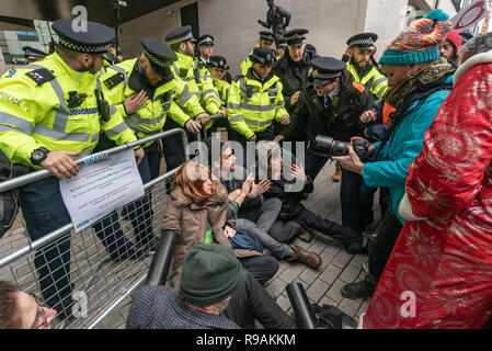 London, UK. 21st December 2018. Climate campaigners from Extinction Rebellion sit down and lock on in front of the BBC Plaza calling it to stop ignoring the climate emergency & mass extinctions taking place and promoting destructive high-carbon living through programmes such as Top Gear and those on fashion, travel, makeovers etc. The protest, organised by the Climate Media Coalition (CMC) and its director Donnachadh McCarthy brought mannequins wrapped in white cloth to the BBC representing the bodies of a Greek village killed by fire. Peter Marshall/Alamy Live News - Stock Image