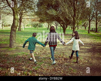 Mother, son and daughter walk in park. - Stock Image