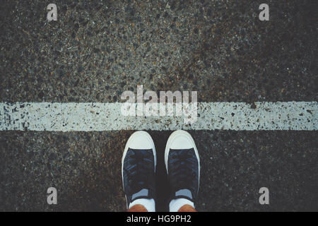 Male feet in white socks and gumshoes standing near grunge white line on gray asphalted road, ready to go - Stock Image