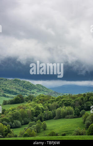 Stormy weather with dramatic rainy clouds over green peaks in Carpathian Mountains, Bieszczady,Poland. - Stock Image