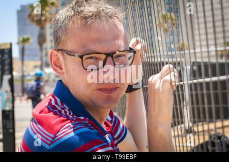 Attractive Caucasian young man looking through the steel grating fence before him. Looking for a solution concept, overcoming difficulties - Stock Image