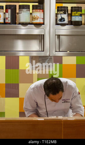 Male chef preparing food in the kitchen of restaurant Cafe Mosaic in the Carlton Hotel Singapore. - Stock Image