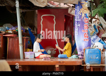 Two young girls playing the game of cards Uno in a shack surrounded by clutter, in Phnom Penh, Cambodia. - Stock Image