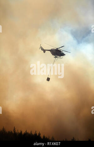 Helicopter fighting fire at Burnside, Dunedin, South Island, New Zealand - Stock Image