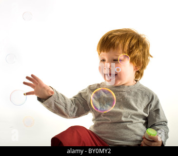 A little boy blowing soap bubbles on white - Stock Image