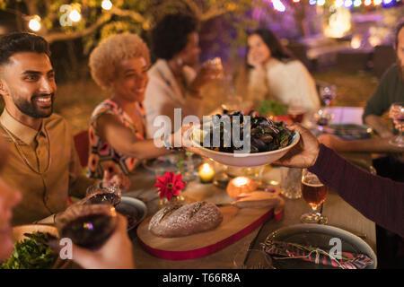 Friends passing mussels, enjoying dinner garden party - Stock Image