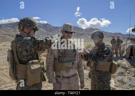 U.S. Marine Maj. Gen. David J. Furness, left, the commanding general, and Sgt. Maj. Alex M. Dobson, the sergeant major, 2nd Marine Division meritoriously promote Lance Cpl. Patrick C. Mulcahy, a section leader with 2nd Light Armored Reconnaissance Battalion, 2nd Marine Division to the rank of Corporal, at Fort Irwin, California, March 12, 2019. Mulcahy was recognized by Maj. Gen. Furness for his superior performance of duties and meritoriously promoted to the rank of Corporal. The Marines of 2d Light Armored Reconnaissance Battalion participated in National Training Center 19-05 as the opposin - Stock Image