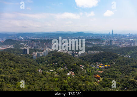 Taipei, Taiwan with suburbs and green rolling hills with Xinyi Business District in far distance as the urban area encroaches on the environment. - Stock Image