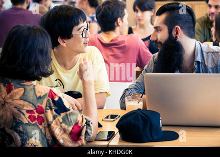 Man using laptop chatting with companion - Stock Image