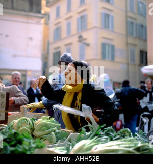 An elderly woman buying cauliflower vegetables in autumn at a stall in Campo dei Fiori market Rome Italy  KATHY DEWITT - Stock Image