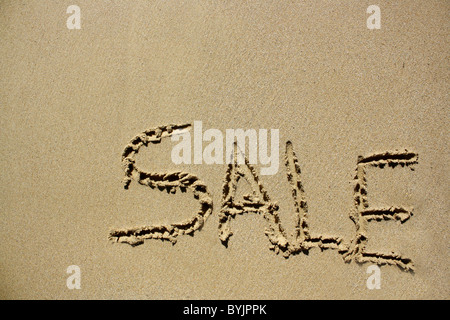 'Sale' written out in wet sand. Please see my collection for more similar photos. - Stock Image
