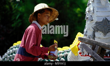 A Shan refugee from Burma (Myanmar) decorating a new Buddhist temple with yellow paint in northern Thailand. - Stock Image
