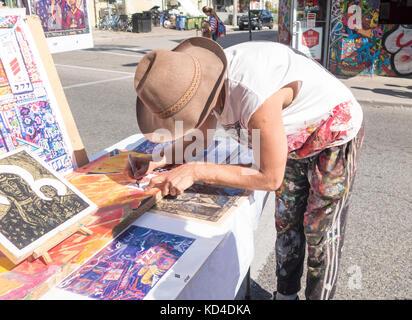 Street artist Steel Daniels autographs a postcard of his artwork in Kensington Market in downtown Toronto Ontario - Stock Image