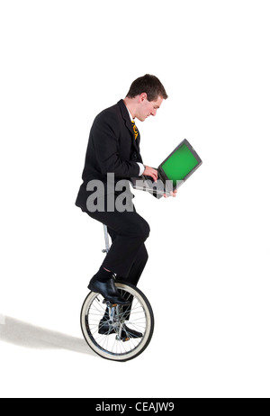 photograph of businessman on unicycle with laptop computer - Stock Image