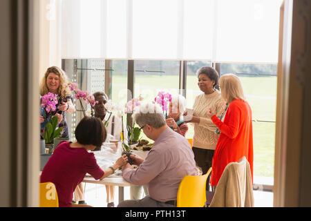Active seniors enjoying flower arranging class in community center - Stock Image