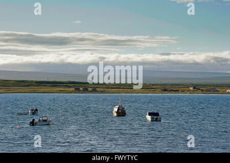 Fishing boats moored at the coast near Ekkerøy at Varangerfjorden in arctic Norway seen in the light of the - Stock Image