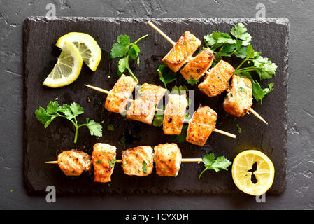Barbecue salmon skewers on slate board over black stone background. Top view, flat lay - Stock Image