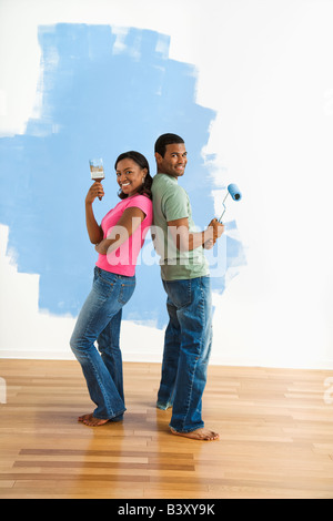 African American couple next to half painted wall as they stand back to back with paint utensils - Stock Image