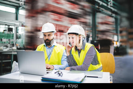 A portrait of a mature industrial man and woman engineer with laptop and smartphone in a factory, working. - Stock Image