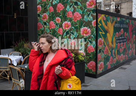 A parting hug from friends and the temporary construction hoarding in Broadwick Street, Soho, on 5th March 2019, in London, England. - Stock Image