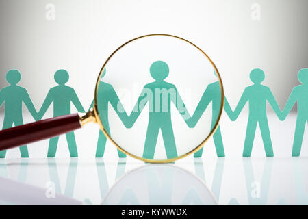 Paper Cut Out Human Figure Seen Through Magnifying Glass - Stock Image