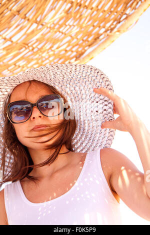 Young girl in a hat in summer relaxing on the beach - Stock Image