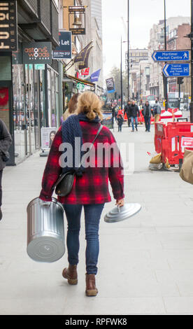 Woman walking through central London carrying a dustbin and lid - Stock Image