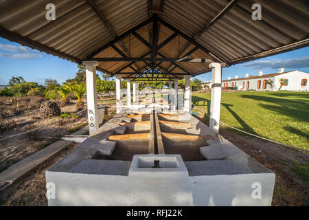 Roofed hand laundry building close to former tuna fishermen huts of Praia do Barril, Algarve, Portugal - Stock Image