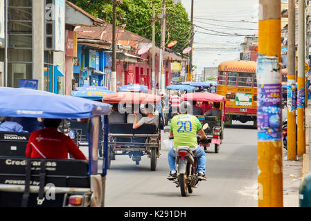 Very busy street in Iquitos, Peru. The popular mototaxis, a type of rickshaw, is the most popular form of the public transport in the city. - Stock Image