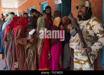 (190423) -- SRINAGAR, April 23, 2019 (Xinhua) -- An Indian paramilitary trooper stands guard as voters stand in a queue to cast their ballots at a polling station at Chaklipora village of Anantnag district, about 85 km south of Srinagar, the summer capital of Indian-controlled Kashmir, April 23, 2019. Voting began Tuesday in Anantnag district of Indian-controlled Kashmir during the third phase of India's 17th general elections. (Xinhua/Javed Dar) - Stock Image