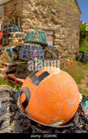 Lobster and crab pots stored above the harbour wall at Inner Hope Cove in the 'South Devon Area of Outstanding - Stock Image