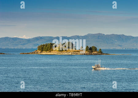 September 17, 2018 - Tongass Narrows, AK: Small aluminum hull fishing boat passing by Guard Islands and old lighthouse, early morning, near Ketchikan. - Stock Image