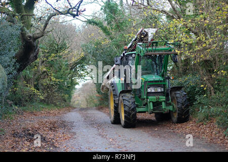 A farm vehicle parked on a country lane. - Stock Image