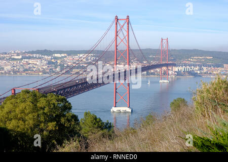 25 de Abril bridge (April 25 bridge) connects the city of Lisbon to Almada on the south bank crossing the river Tagus - Stock Image