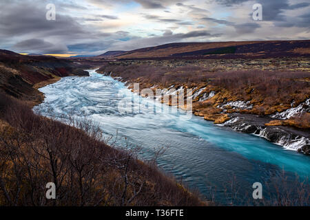 Hraunfossar ('Lava Falls' in English) in Borgarfjörður district is a series of beautiful waterfalls formed by rivulets streaming out of the Hallmundar - Stock Image
