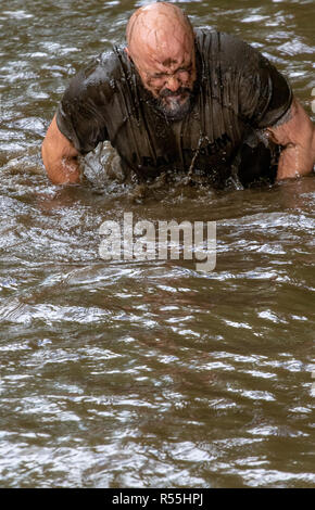 Male mud runner washes at a water crossing - Stock Image