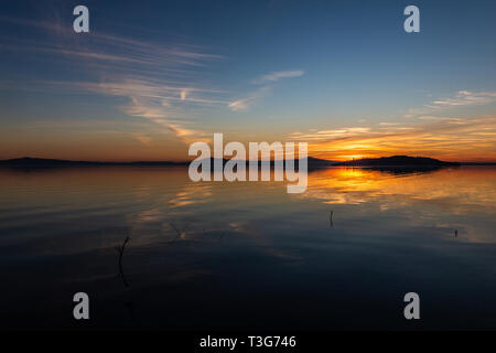 Symmetrcal, beautiful view of Trasimeno lake (Umbria, Italy) at sunset, with orange and blue tones in the sky - Stock Image