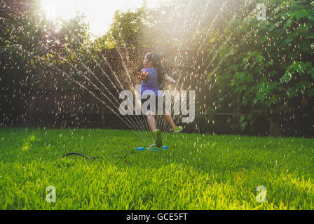 small girl blowing a dandelion during the magic hour - Stock Image