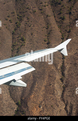 Wing of aeroplane flying through a steep narrow valley on approach to Paro, Bhutan - Stock Image
