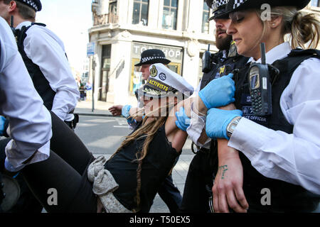 Oxford Circus, London, UK. 19th Apr, 2019. An environmental activist is arrested by the police in Oxford Circus on the fifth day of the climate change protest by the Extinction Rebellion movement group. A large number of police presence around the pink yacht as they un-bonding the activist who glued themselves and the police prepare to remove them from the site. According to the Met Police, nearly 700 activists have been arrested since the demonstration started on 11 April 2019. Credit: Dinendra Haria/Alamy Live News - Stock Image
