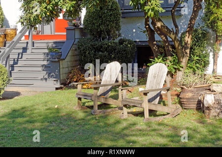 A pair of Adirondack style wooden rocking chairs on the front lawn of a house - Stock Image