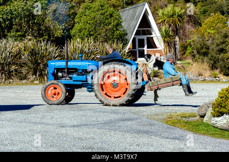 Men and dog on tractor - Stock Image