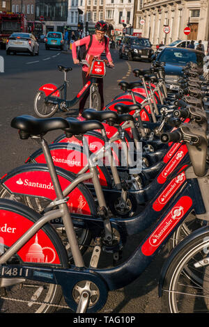 TFL Santander sponsored London red rental hire bikes in Southwark Street with female cyclist about to start her hire ride from the bike terminal docking station. Transport for London Southwark London UK - Stock Image