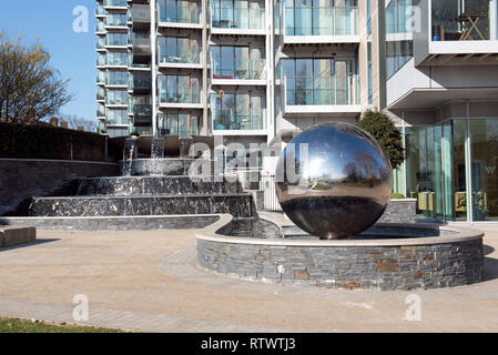 Mirror ball waterfall sculpture with waterfall and modern flats or appartments behind, Berkeley Homes Woodberry Down, Stoke Newington Hackney London E - Stock Image