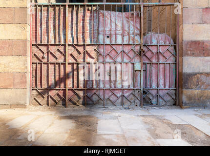Background of old weathered grunge antique wrought iron gate with geometrical pattern ornaments and stone bricks wall - Stock Image