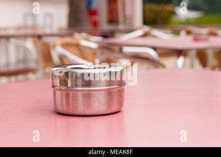Steel ashtray on a table outside a hotel bar. - Stock Image