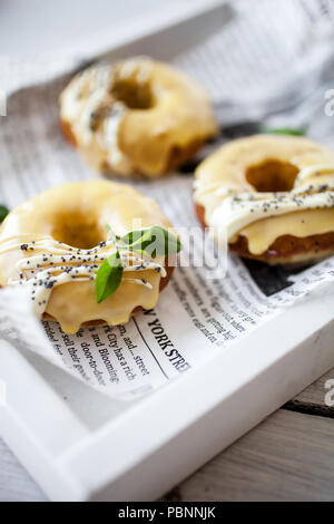 Lemon donuts with white chocolate and poppy seeds - Stock Image