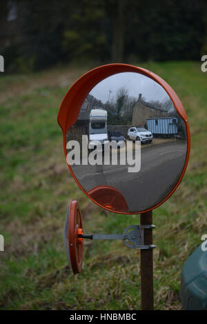 Convex safety mirror opposite a house in the north Oxfordshire village of Hook Norton - Stock Image